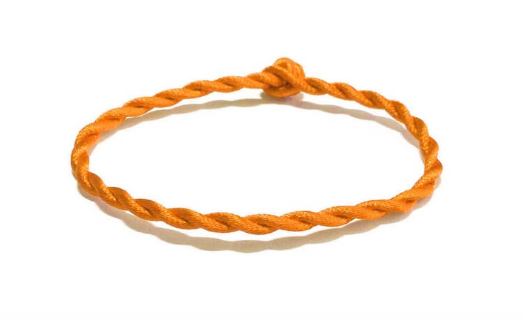 Оранжевая нить на запястье